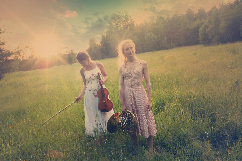 Dalasinfoniettans Anna Rahile, viola och Christina Landén, horn, på en äng i motljus