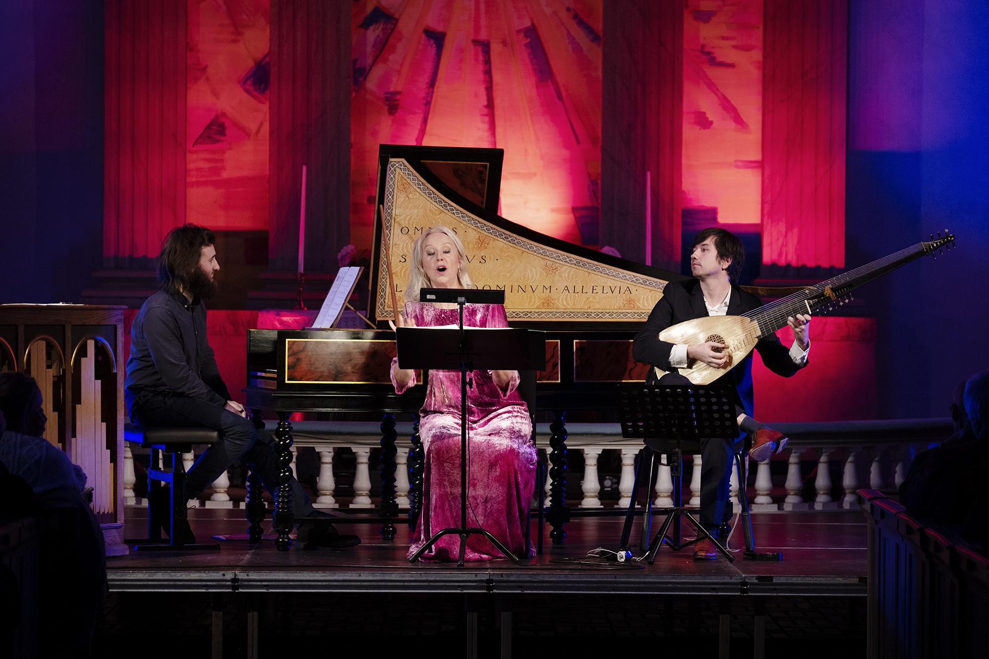 En trio spelar i en ljussatt kyrka