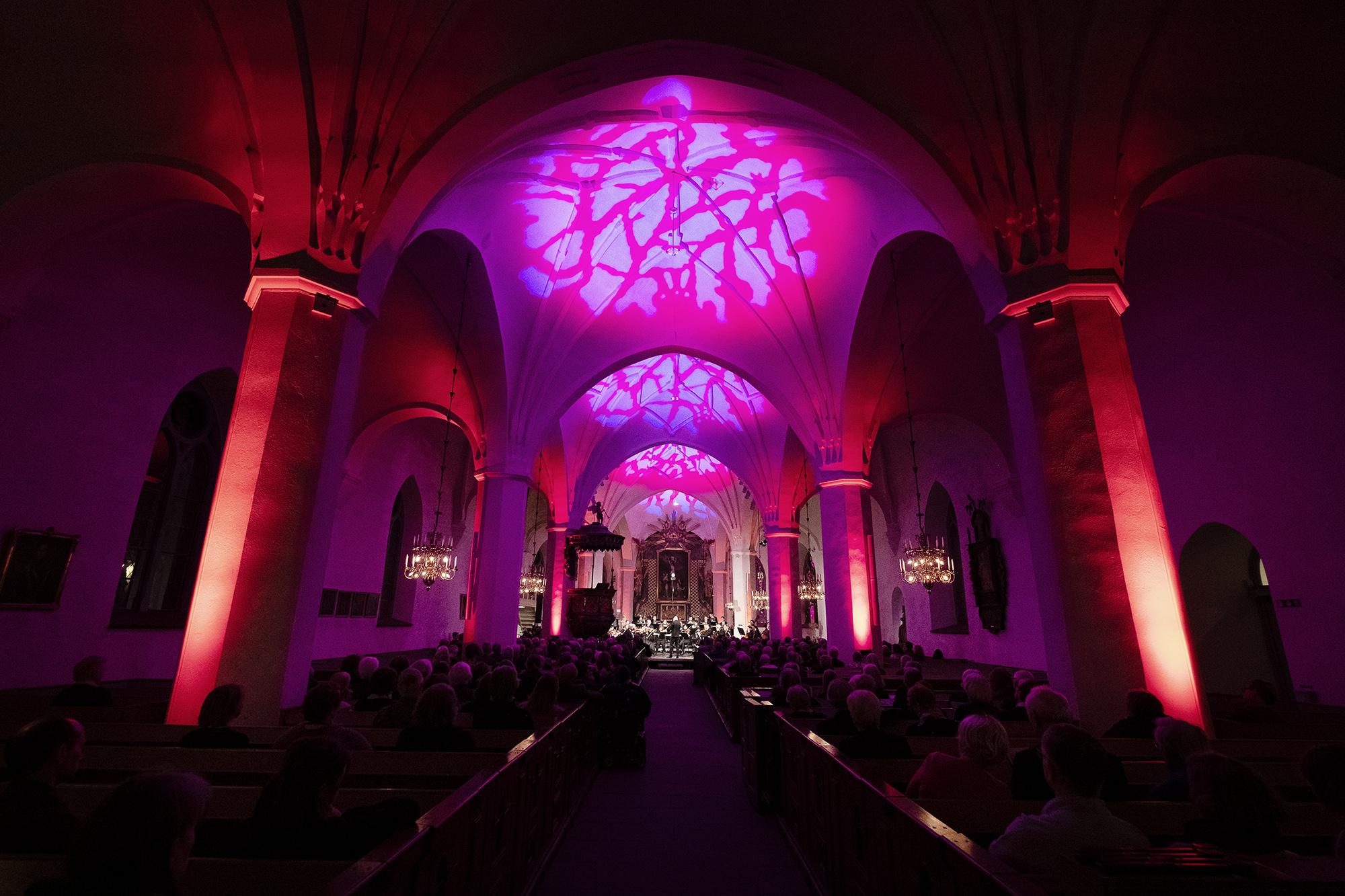 En rosaskimrande kyrka med fulla bänkrader och Dalasinfoniettan på scen