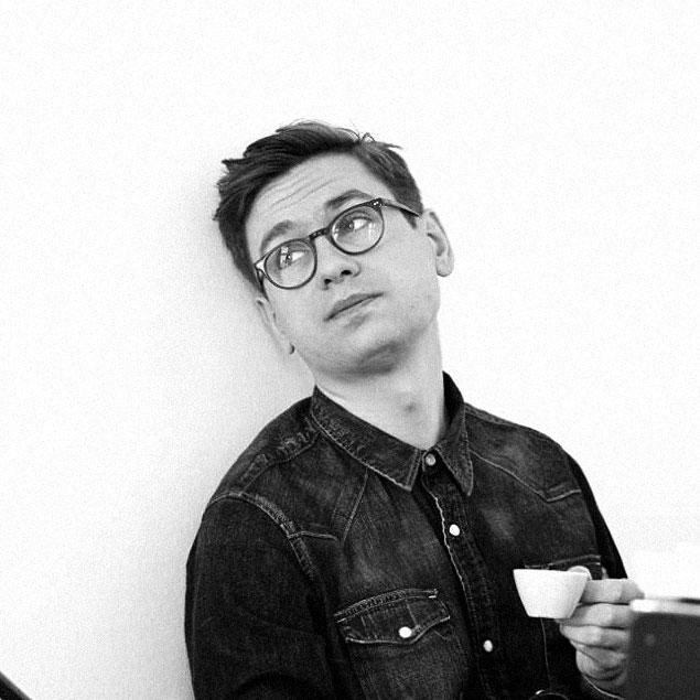 Víkingur Ólafsson litad mot vit vägg med kaffekopp i handen